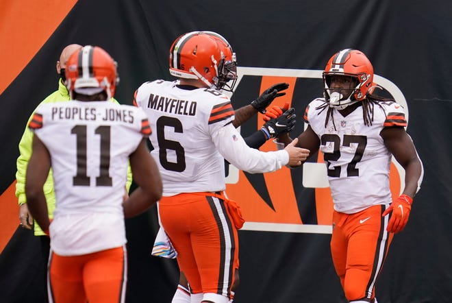 The Browns' Kareem Hunt, right, celebrates a touchdown with quarterback Baker Mayfield, center, during the second half Sunday against the Bengals in Cincinnati.