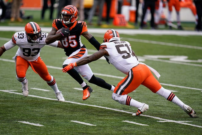 Cincinnati Bengals' Tee Higgins (85) makes a touchdown reception against Cleveland Browns' B.J. Goodson (93) and Mack Wilson (51) during the second half of an NFL football game, Sunday, Oct. 25, 2020, in Cincinnati. (AP Photo/Michael Conroy)