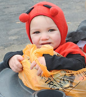 One-year-old Alison Terrell holds a bag of candy during a Trunk-and-Treat event Saturday at Alliance Church of the Nazarene.