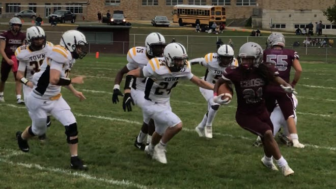 Holy Cross running back Darrell Jackson (21) tries to turn the corner with a host of Bordentown tacklers in pursuit during Saturday's West Jersey Football League game. Jackson ran for two touchdowns, but Bordentown won, 25-20.