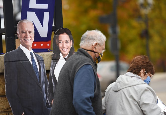 """Biden supporters walk past a cardboard cutout of Joe Biden and Kamala Harris during a rally at Riverwalk Park in New Castle, Saturday afternoon. The day started with a """"Ridin' with Biden"""" caravan in Ewing Park in Ellwood City."""