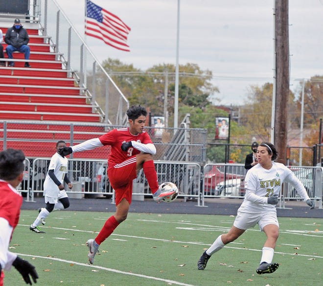 Orrville Deninssonn Lopez heads upfield in front of St. Vincent-St. Mary defender Andrew Powell.
