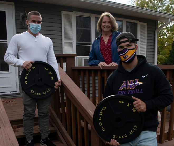 Spencer Chaput (left) and Zach Leinenbach (right) display some of the weights that Sheila Foreman gave them recently. The young men returned Foreman's generosity, raking the leaves at her Alfred home.