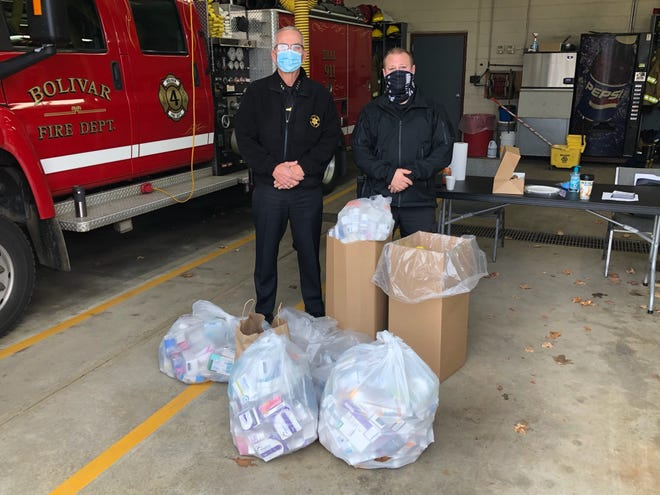 Allegany County Sheriff Rick Whitney, left, and Bolivar Police Chief Steve McPherson stand in front of medications brought in by community members at the Bolivar Pill Drop.