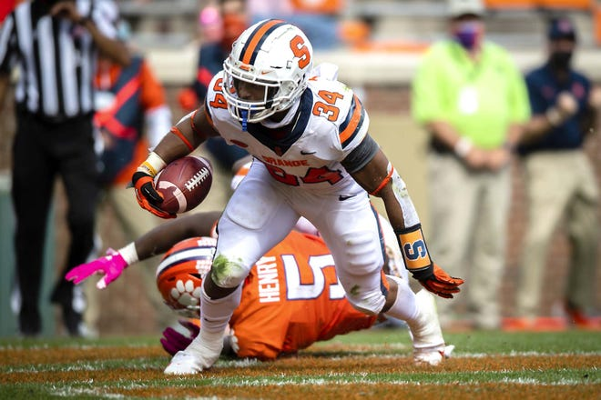 Syracuse running back Sean Tucker (34) gets past Clemson defensive end K.J. Henry on a touchdown run during Saturday's game in Clemson, South Carolina.