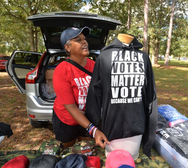 DeWyna Robinson of Teedtees sets up her display of T-shirts and caps Sunday at Lonnie Miller Park adjacent to the Legends Community Center, 5130 Soutel Drive. The community center is an early voting site. Robinson was among those participating in the nonpartisan Souls to the Polls event designed to encourage Black residents to vote early before the Nov. 3 general election.