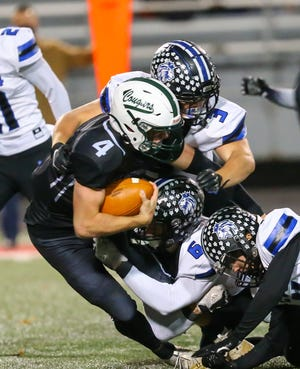 CVCA's Kyle Snider (3) and Grant Simmons (6) tackle Lak Catholic quarterback Joe Malchesky during the Royals' 35-21 loss Oct. 24 to the Cougars in Mentor.