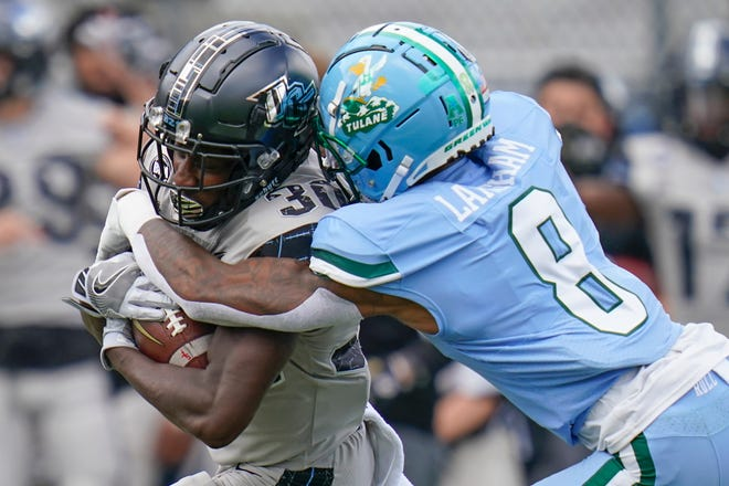 Central Florida running back Greg McCrae, left, is tackled by Tulane cornerback Willie Langham (8) after a gain during the first half Saturday in Orlando.