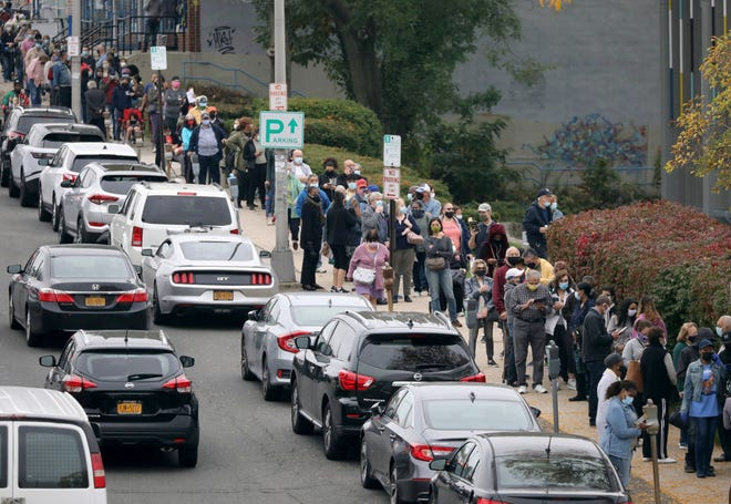 Voters line up in front of the Yonkers Public Library in Yonkers, N.Y., on Saturday as the first day of early voting in the presidential election began across New York state.