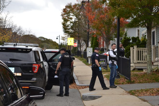 Members of the Newport Police Department investigate at a house on John H. Chafee Boulevard on Sunday after shots allegedly were fired earlier in the day.