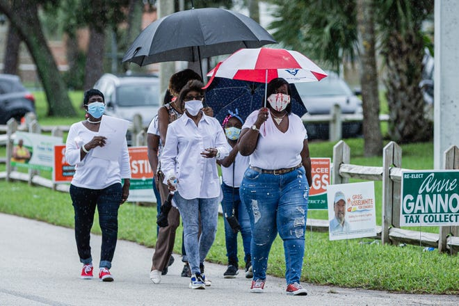 A group of friends walks under umbrellas during a light rain to the polling place at the Wells Recreation Center in Riviera Beach, Sunday, October 25, 2020. The group Black Men Stand Up organized an event to ensure at least 500 Black men voted on Sunday.