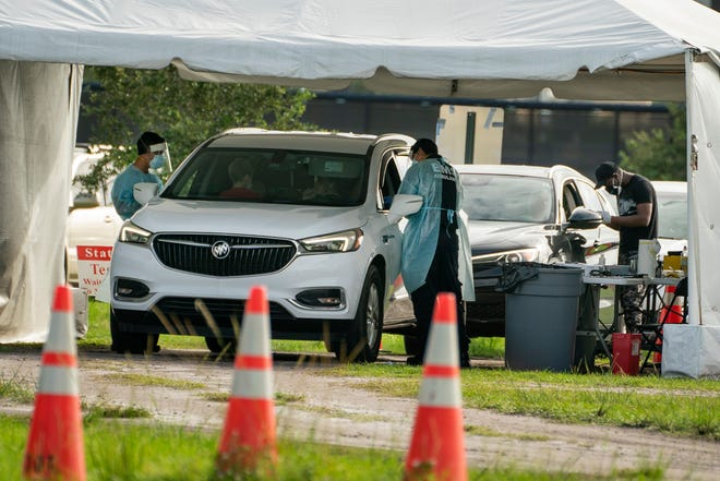 People wait in their cars to be tested for the coronavirus at a drive-up rapid testing site at the FitTeam Ballpark of the Palm Beaches in West Palm Beach on Friday.