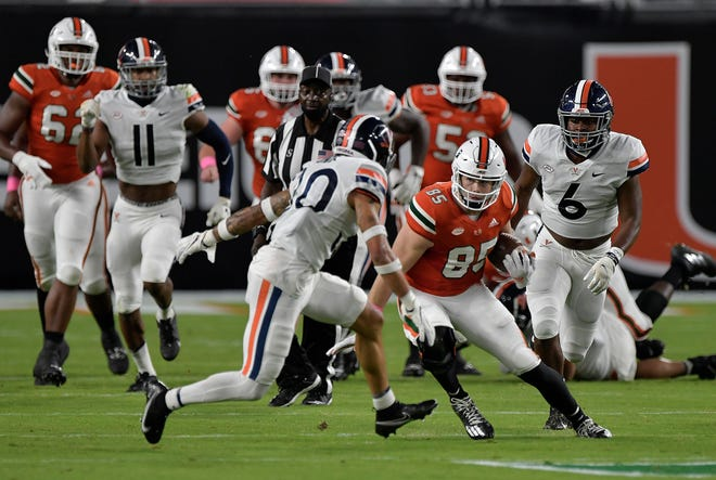 Miami tight end Will Mallory runs past Virginia defensive back D'Angelo Amos during the first half of their game, Saturday, October 24, 2020.