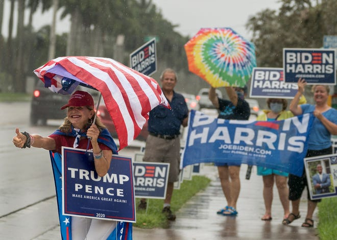 Gisela Garneau shows her support for President Donald Trump outside an early voting site at the Palm Beach County Library  in West Palm Beach, Florida on October 21, 2020.  (GREG LOVETT / The Palm Beach Post)