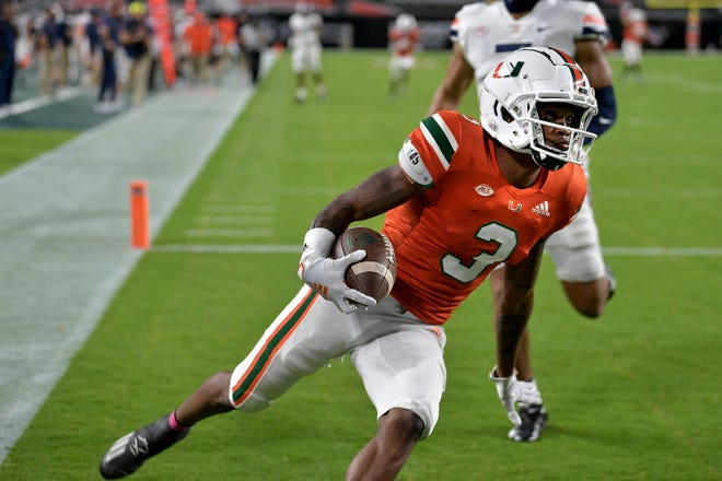 Miami receiver Mike Harley catches a touchdown pass in front of Virginia linebacker Noah Taylor during the first half of Saturday's game.