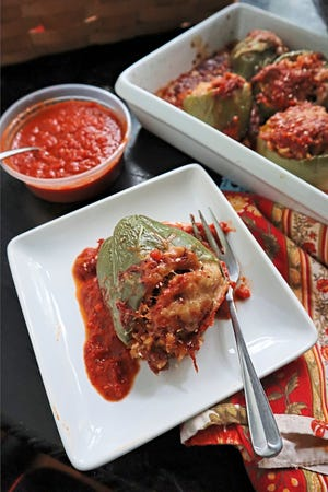 Bell peppers stuffed with a cheesy mixture of sweet Italian sausage, brown rice and Parmesan cheese make a hearty fall meal. [Pittsburgh Post-Gazette/TNS]