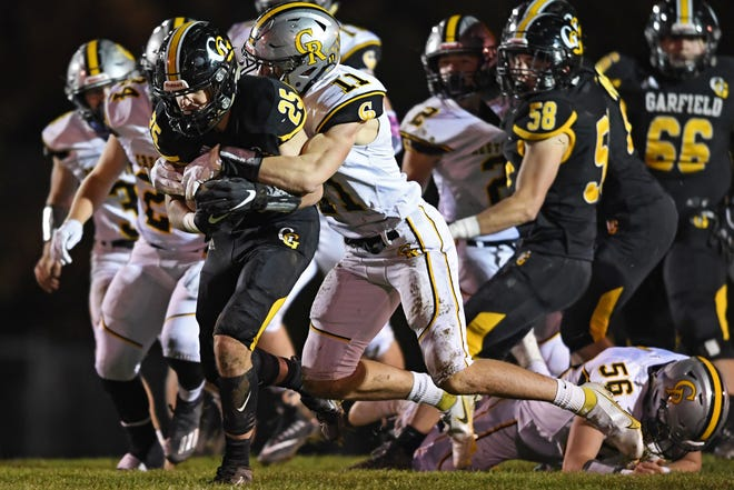 Garfield's Anthony Demma is tackled by Crestview's William Hardenbrook during the first half of their OHSAA playoff game Saturday.