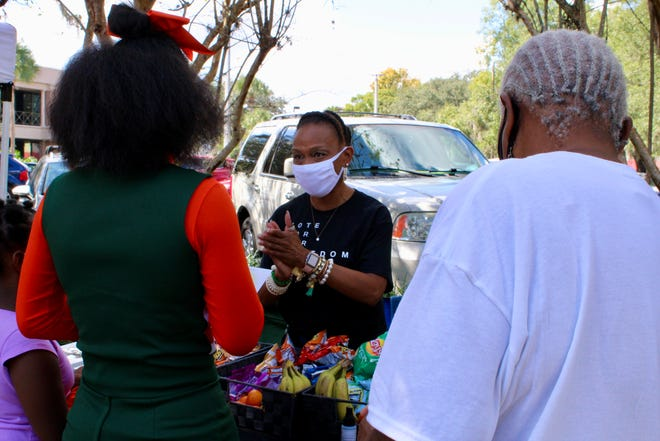 Terrie Ellerbe, a member of the nonprofit group March for Our Freedom, speaks with P.U.S.H. the Vote attendees on Sunday at the Supervisor of Elections Office in Gainesville.. The group handed out snacks and drinks to those heading to the polls.
