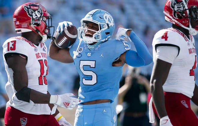 North Carolina's Dazz Newsome enjoys a moment with N.C. State's Tyler Baker-Williams, left, and Cecil Powell, right, nearby during Saturday's game at Kenan Stadium.