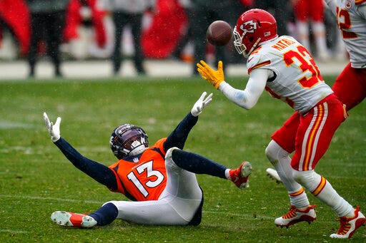 Denver Broncos wide receiver K.J. Hamler, left, falls as Kansas City Chiefs strong safety Tyrann Mathieu intercepts a pass during the second half on Sunday at Empower Field at Mile High in Denver. (AP Photo/Jack Dempsey)
