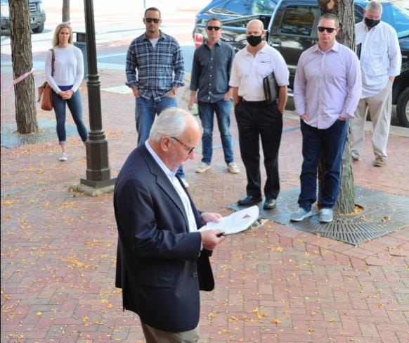 Representatives of High Rock Group and other onlookers listened as Paul R. Cooper, vice president of Alex Cooper Auctioneers, read legal documents before asking for bids on the Leitersburg Cinema Properties.