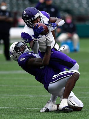 Abilene Christian wide receiver L.J. McConnell is tackled by Stephen F. Austin's Myles Brooks after catching a pass in overtime during the Oct. 24 game at Globe Life Park in Arlington. Both schools are expected to join the Western Athletic Conference beginning the 2022 season.