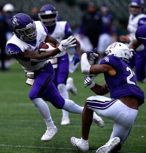 Abilene Christian running back Jermiah Dobbins pushes away Stephen F. Austin free safety Ja'Terious Evans during the Oct. 24 game at Globe Life Park in Arlington. SFA won 35-32 in overtime.