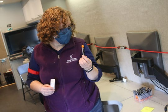 Kitsap Public Health Specialist Amy Anderson holds a tube through the nose inside the county Emergency Operations Center mobile command vehicle.