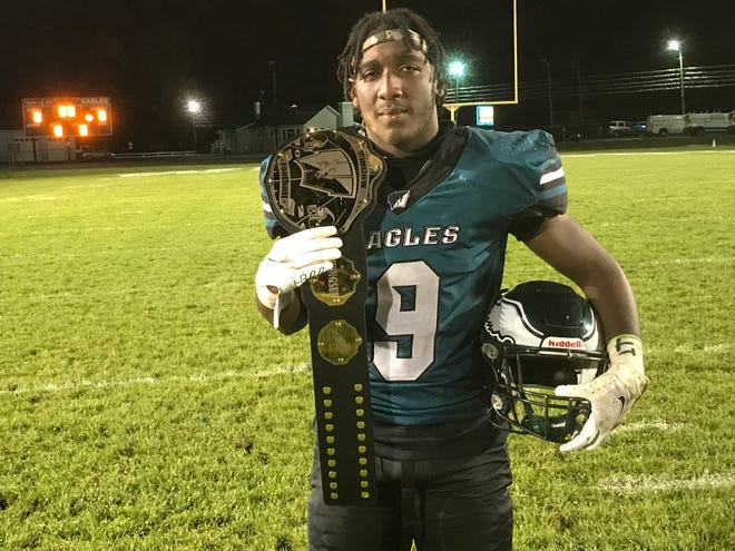 Junior linebacker Emeril Mitchell proudly shows off the turnover belt he earned with two takeaways, one resulting in a score, during Winslow Township's 32-14 win over Washington Township on Saturday.