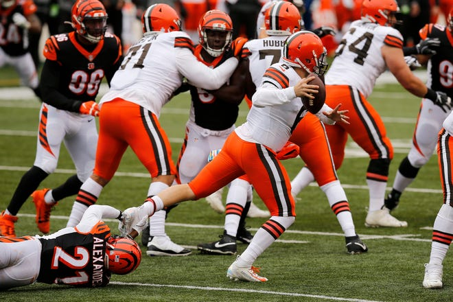 Cleveland Browns quarterback Baker Mayfield (6) escapes a tackle from Cincinnati Bengals cornerback Mackensie Alexander (21) to make a throw in the fourth quarter of the NFL Week 7 game between the Cincinnati Bengals and the Cleveland Browns at Paul Brown Stadium in downtown Cincinnati on Sunday, Oct. 25, 2020. The Bengals and Browns exchanged late touchdowns, finishing in a 37-34 win for the Browns.