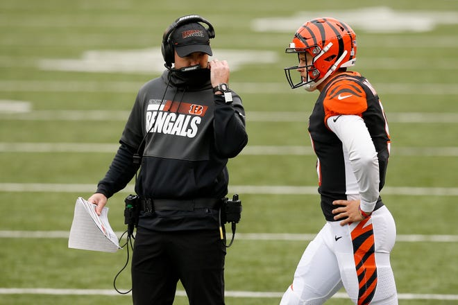 Cincinnati Bengals head coach Zac Taylor and quarterback Joe Burrow (9) discuss a play during a timeout in the fourth quarter of the NFL Week 7 game between the Cincinnati Bengals and the Cleveland Browns at Paul Brown Stadium in downtown Cincinnati on Sunday, Oct. 25, 2020. The Bengals and Browns exchanged late touchdowns, finishing in a 37-34 win for the Browns.