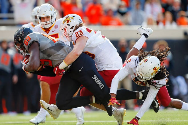 Iowa State linebacker Mike Rose (23) and defensive back Datrone Young (2) try to bring down Oklahoma State tight end Jelani Woods during their Oct. 24 game in Stillwater. The Cyclones might end up winning the Big 12 title, which would probably put them in the Cotton Bowl.