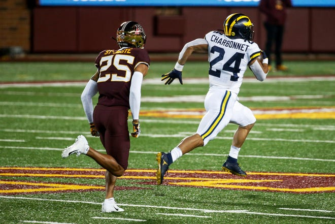 Michigan running back Zach Charbonnet, right, breaks away from Minnesota defensive back Benjamin St-Juste for a 70-yard touchdown run on Saturday in Minneapolis.