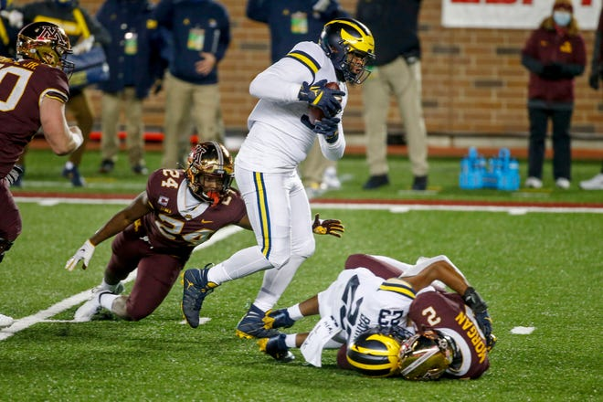 Michigan defensive lineman Donovan Jeter catches the ball en route to a touchdown past running back Mohamed Ibrahim after linebacker Michael Barrett knocked it loose from Minnesota quarterback Tanner Morgan in the first quarter in Minneapolis.
