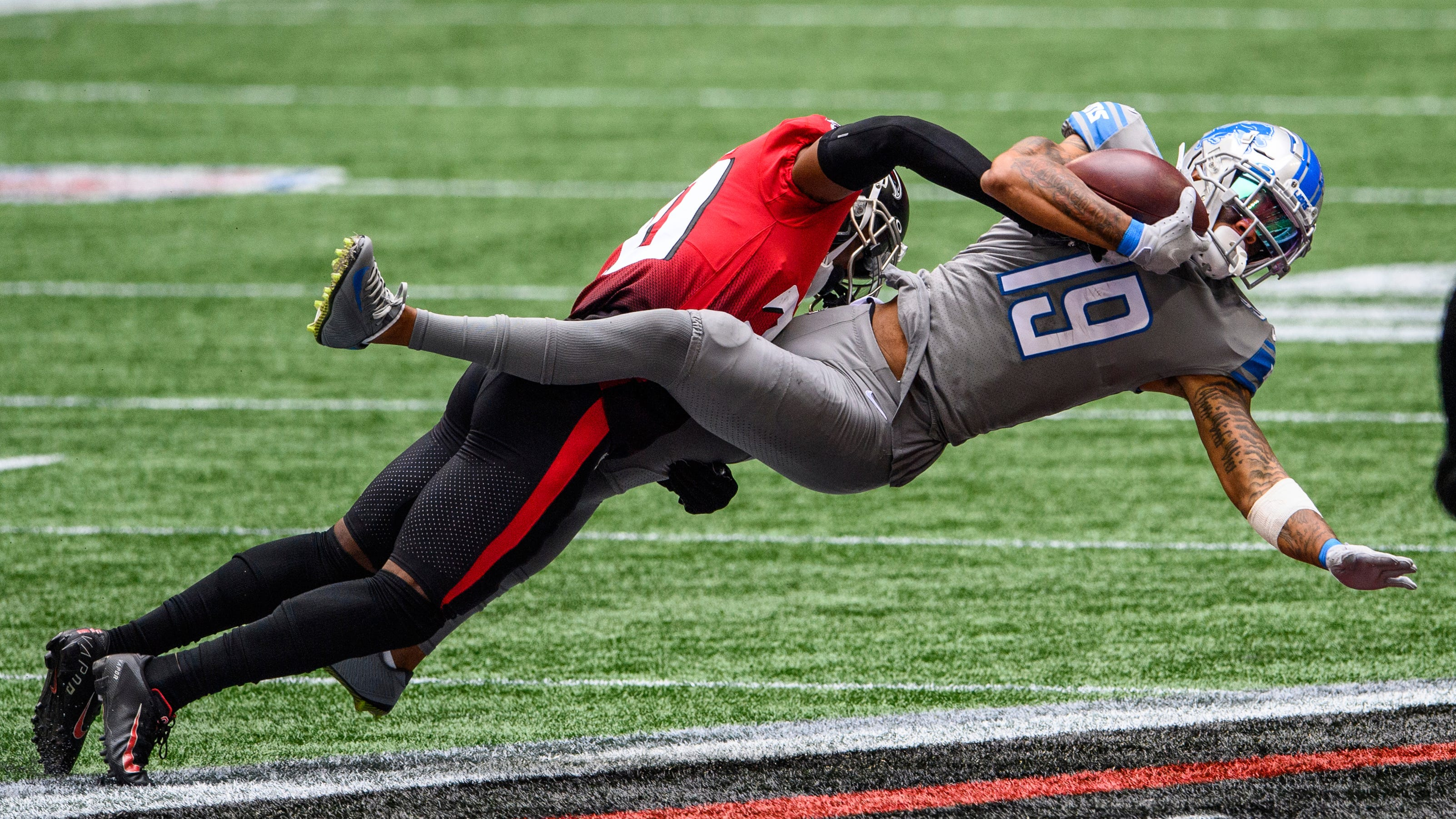 Detroit Lions wide receiver Kenny Golladay is tackled by Atlanta Falcons defensive back Kendall Sheffield.