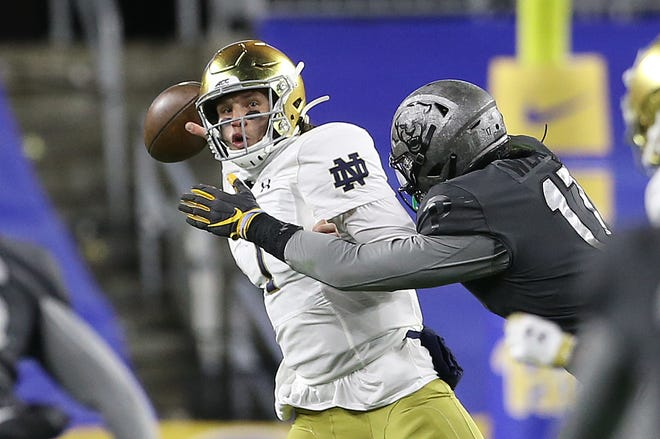Oct 24, 2020; Pittsburgh, Pennsylvania, USA;  Notre Dame Fighting Irish quarterback Brendon Clark (7) throws under pressure from Pittsburgh Panthers defensive lineman Rashad Weaver (17) during the fourth quarter at Heinz Field. The Notre Dame Fighting Irish won 45-3. Mandatory Credit: Charles LeClaire-USA TODAY Sports
