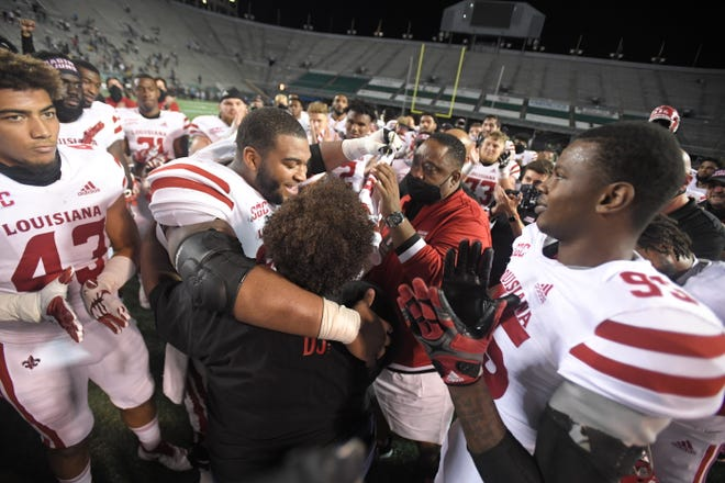 UL center Shane Vallot puts his arms around Sarah Looney and David Looney Sr. after a win over UAB on Friday night at Legion Field in Birmingam honoring their son D.J. Looney, a Ragin' Cajuns assistant coach who died of a heart attack on Aug. 1.