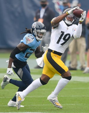 Pittsburgh Steelers wide receiver JuJu Smith-Schuster (19) receives a pass over Tennessee Titans cornerback Tye Smith (23) during the first quarter at Nissan Stadium in Nashville, Tenn., Sunday, Oct. 25, 2020.