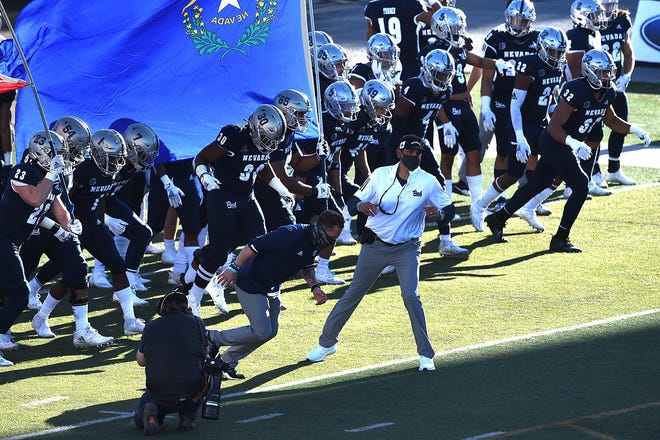 Nevada head coach Jay Norvell leads his team onto the field to take on Wyoming at Mackay Stadium in Reno on Oct. 24.