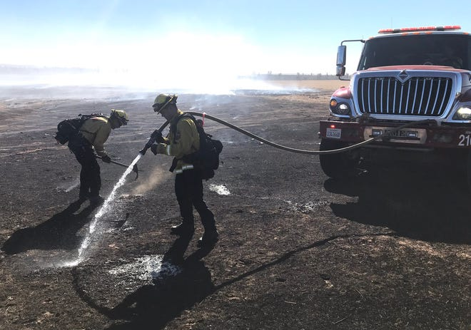 Firefighters extinguish hot spots in the Dersch Fire off Millville Plains Road where the wind was gusting on Sunday, Oct. 25, 2020.The fire burned 133 acres and is 100% contained.