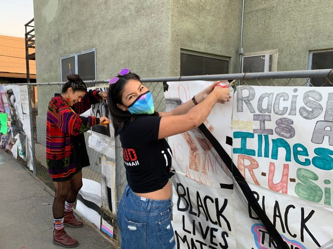Visalia youth remove Black Lives Matter signs from St. Paul's Episcopal Church on Sunday after Visalia Code Enforcement said the signs were in violation of a local ordinance.
