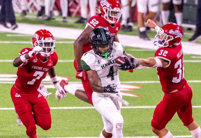 Hawaii's Miles Reed (4) runs between Fresno State's Reggie Strong, left, and Evan Williams on Saturday, October 24, 2020.