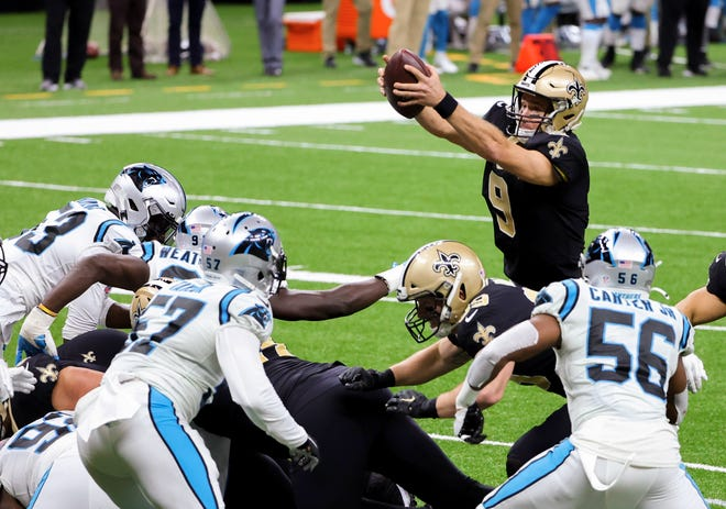 New Orleans Saints quarterback Drew Brees (9) jumps over the line for a touchdown against the Carolina Panthers during the second quarter at the Mercedes-Benz Superdome.