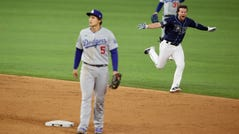 Brett Phillips celebrates after driving in the winning run as Dodgers shortstop Corey Seager and left fielder Joc Pederson walk off the field.