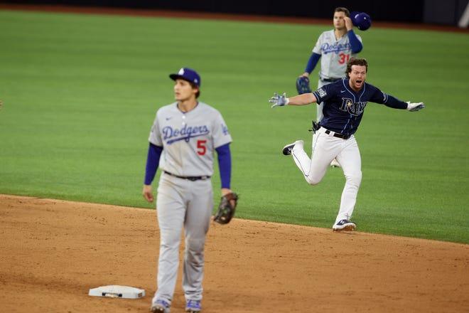 Brett Phillips celebra después de conducir la carrera ganadora cuando el campocorto de los Dodgers Corey Seager y el jardinero izquierdo Joc Pederson salen del campo.