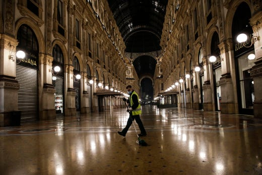 A cleaner sweeps in an empty Vittorio Emanuele II arcade, in Milan, northern Italy, early Sunday, Oct. 25, 2020. Since the 11 p.m.-5 a.m. curfew took effect last Thursday, people can only move around during those hours for reasons of work, health or necessity.