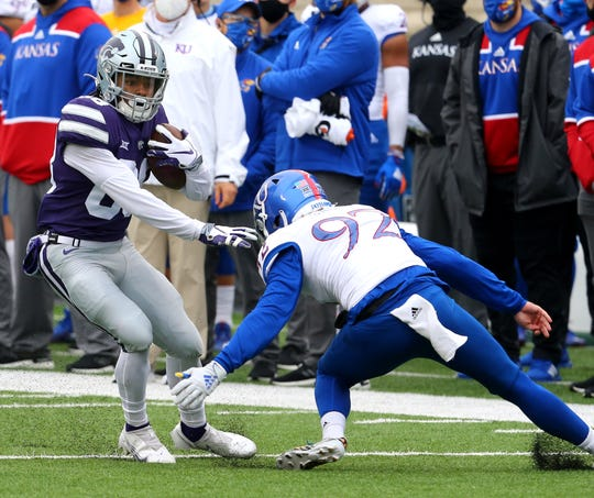 Kansas State wide receiver Phillip Brooks tries to avoid the tackle of Kansas punter Donovan Gagen during a punt return at Bill Snyder Family Football Stadium.