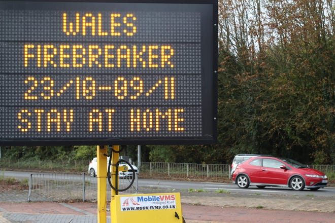 """Traffic passes a COVID-19 sign informing drivers of the """"firebreak"""" lockdown which comes into force from 6:00 pm (1700 GMT), closing non-food retailers, cafes, restaurants, pubs and hotels for two weeks in a bid to reduce soaring coronavirus cases on October 23, 2020 in Cardiff."""
