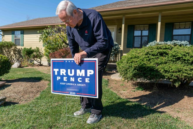 James Porter, 82, of Franklin, a small town between Dayton and Cincinnati, places a Trump/Pence campaign sign in his front yard.
