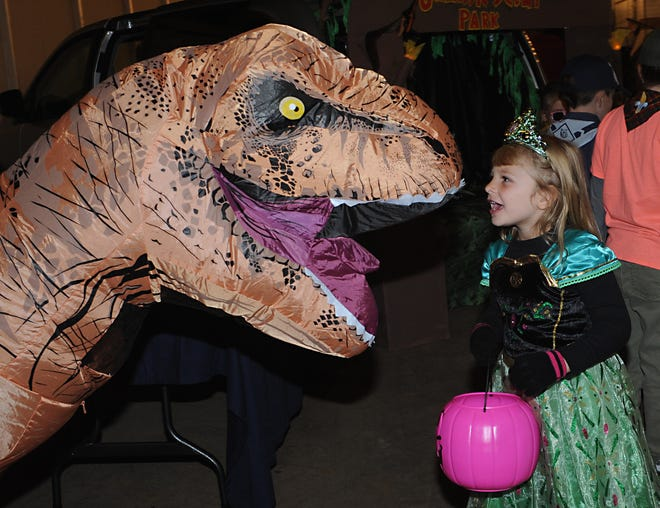Four-year-old Cassady Deckerd goes nose-to-nose with a dinosaur Saturday during a Trunk-or-Treat event at Mile Branch Grange.